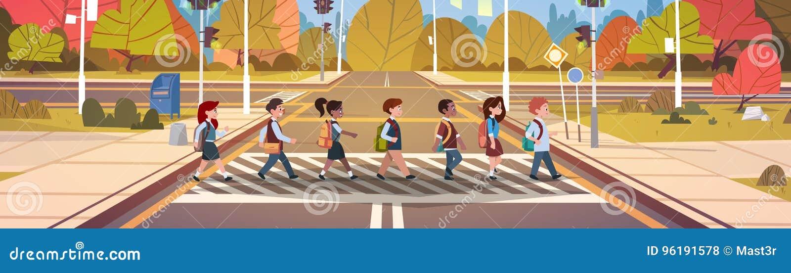 Grupa dziecko w wieku szkolnym Krzyżuje drogę Na Crosswalk Z światłami ruchu