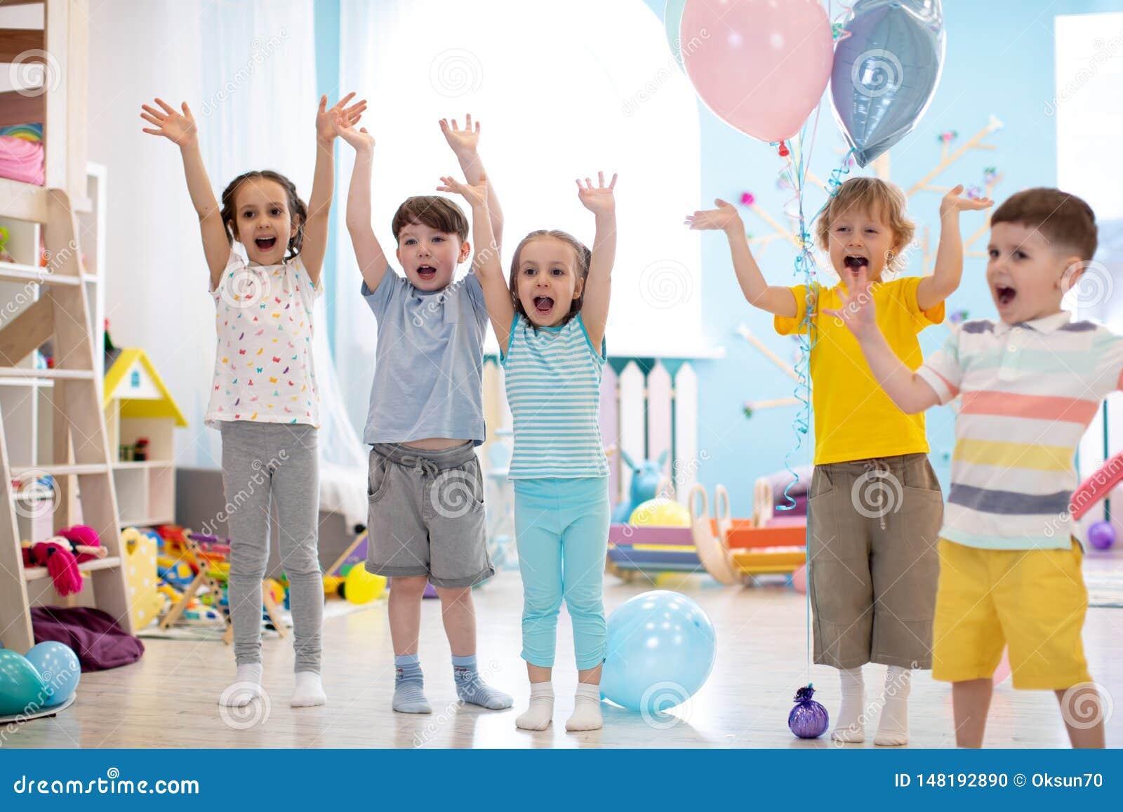 Grupa emocjonalni przyjaciele z ich r?kami podnosi? Dzieciaki zabawy rozrywk? w daycare