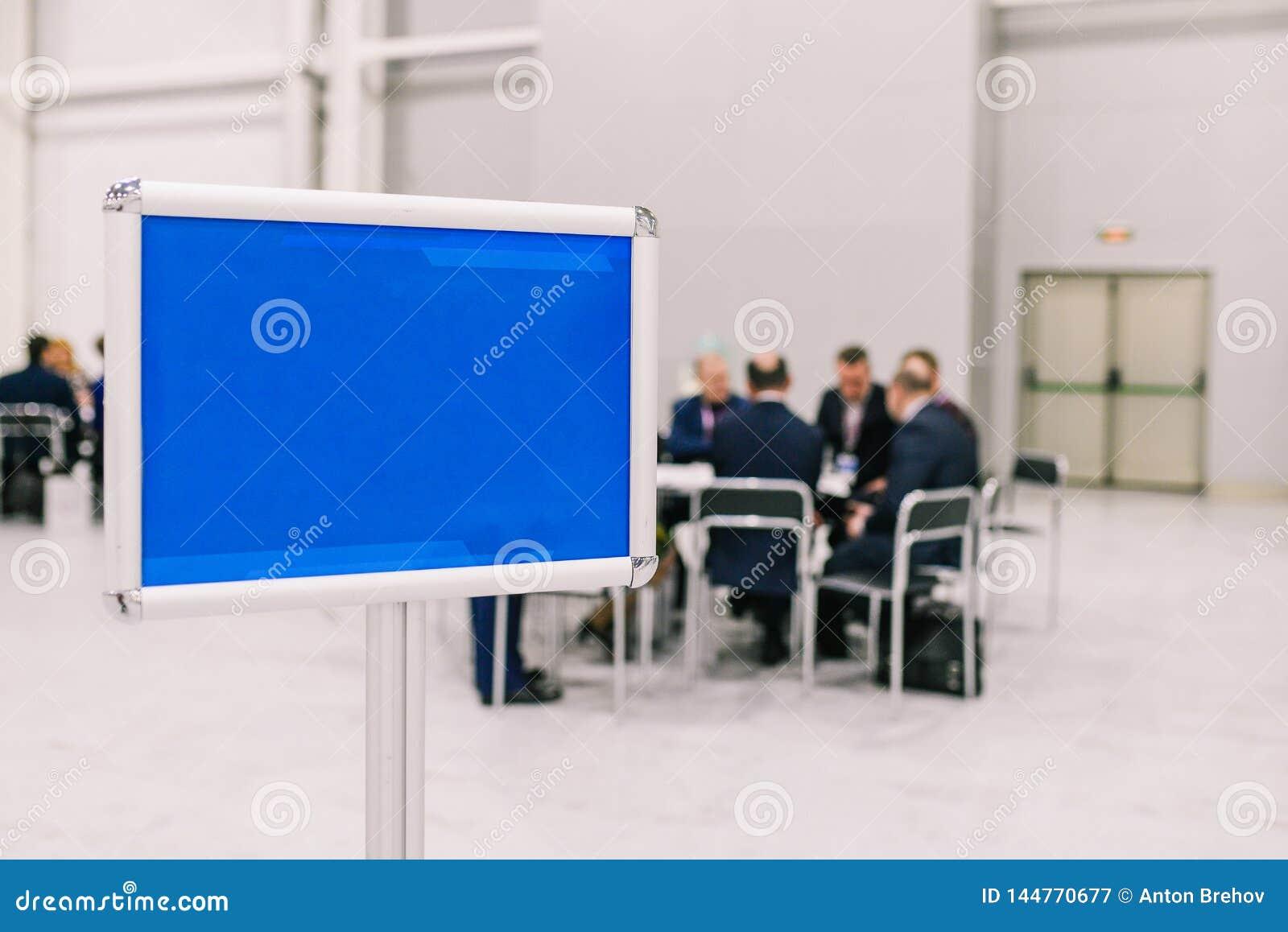 Grupa ludzi dyskutuje projekt M??czy?ni negocjuj? przy sto?em Pusty b??kita talerz Spotyka? personelu i koleg?w