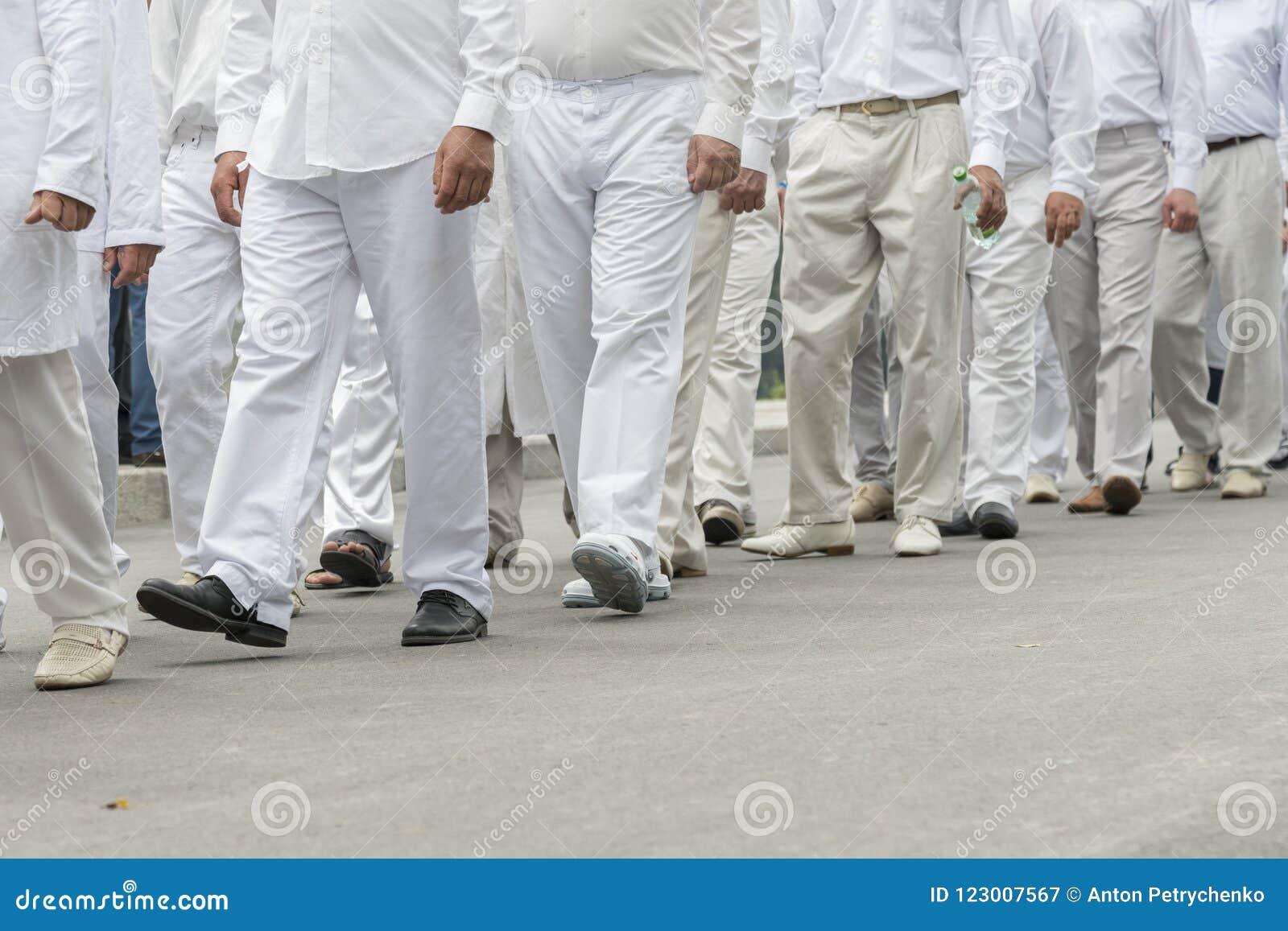 Grupa ludzi w biel ubraniach mężczyzna w białych jeleniach chodzą w dół ulicę