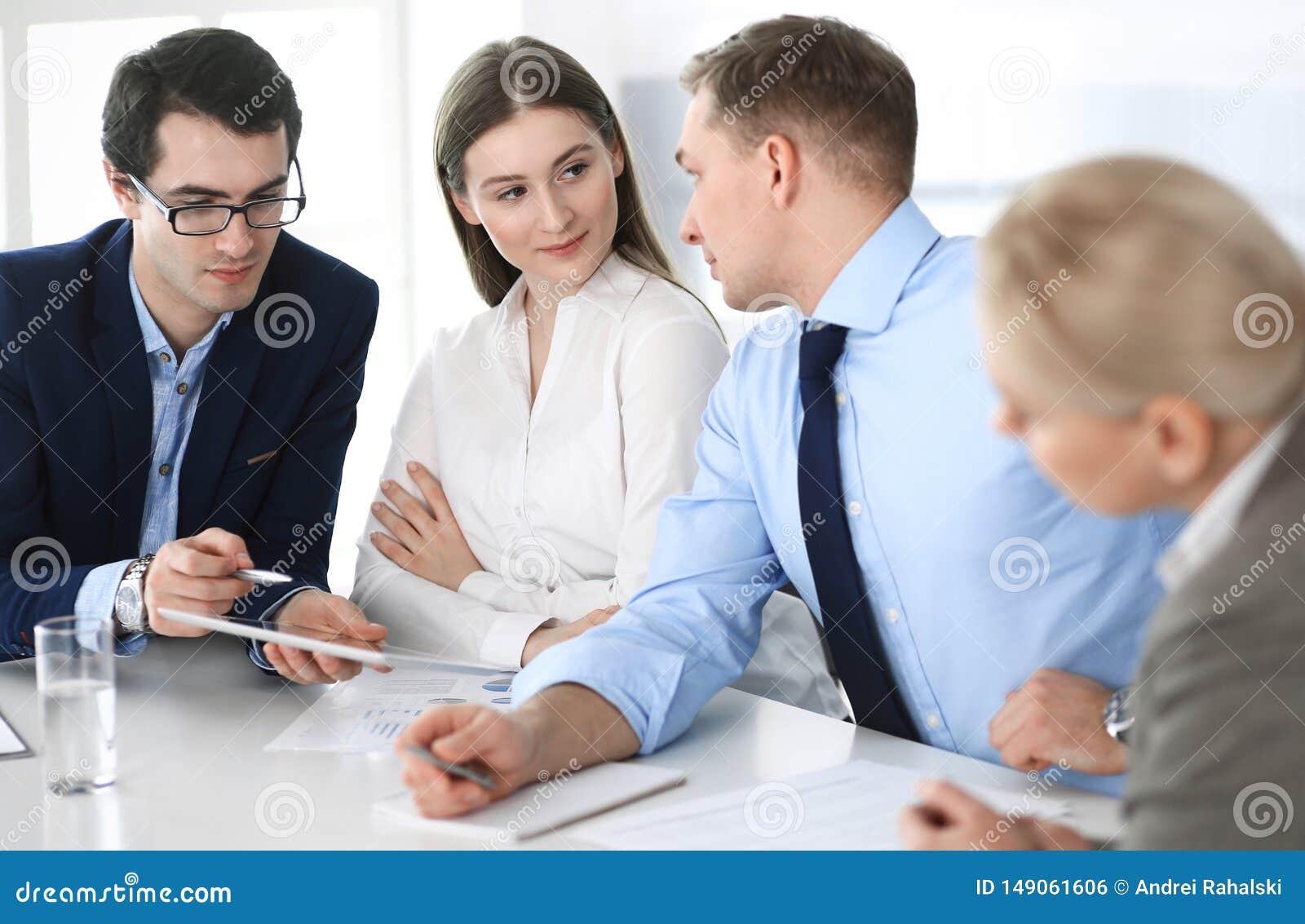 Grupa ludzie biznesu dyskutuje pytania przy spotkaniem w nowo?ytnym biurze Kierownicy przy negocjacj? lub brainstorm