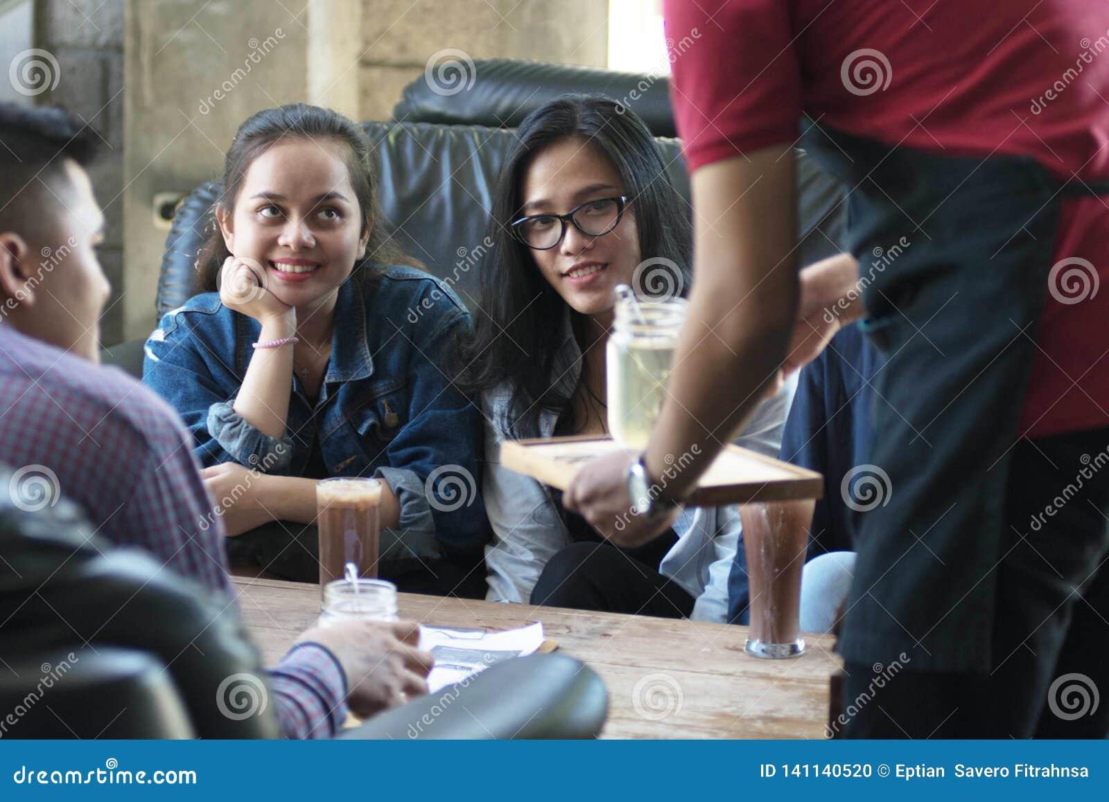 Grupa młody szczęśliwy przyjaciel otrzymywa jedzenie, napój od przy i kelnerów i serweru kawiarnią i restauracją