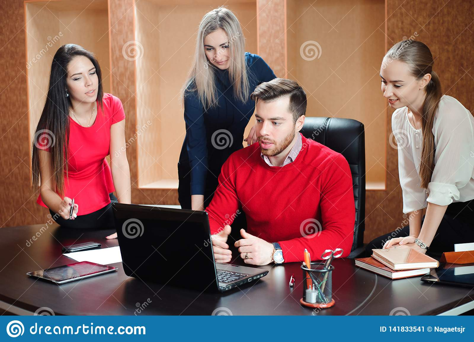 Grupa młodzi koledzy używa laptop przy biurem