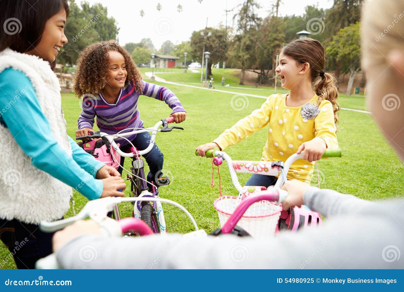 Grupa młode dziewczyny Z rowerami W parku