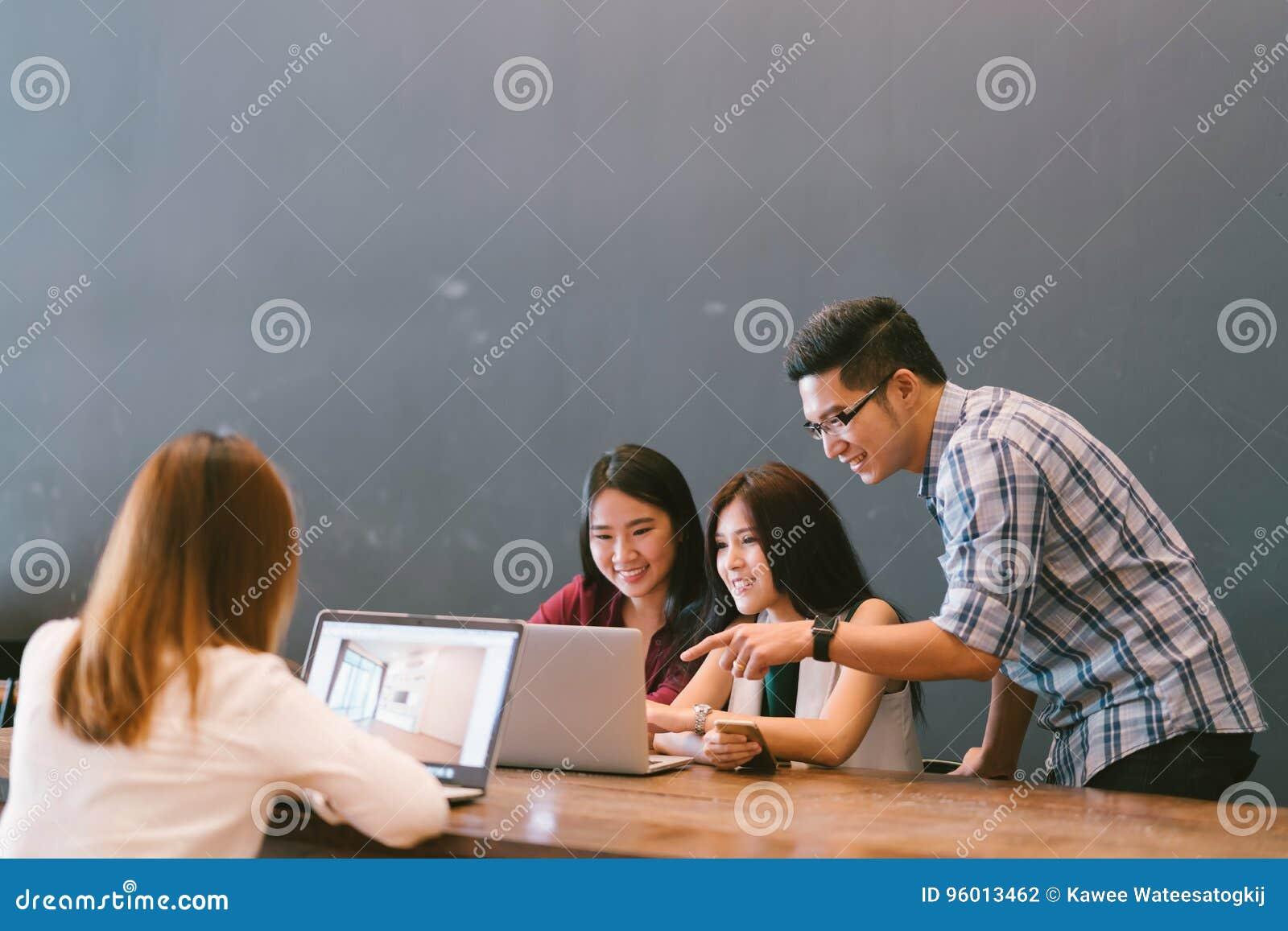Grupa młodzi Azjatyccy biznesowi koledzy w drużynowej przypadkowej dyskusi, początkowego projekta biznesowy spotkanie lub szczęśl