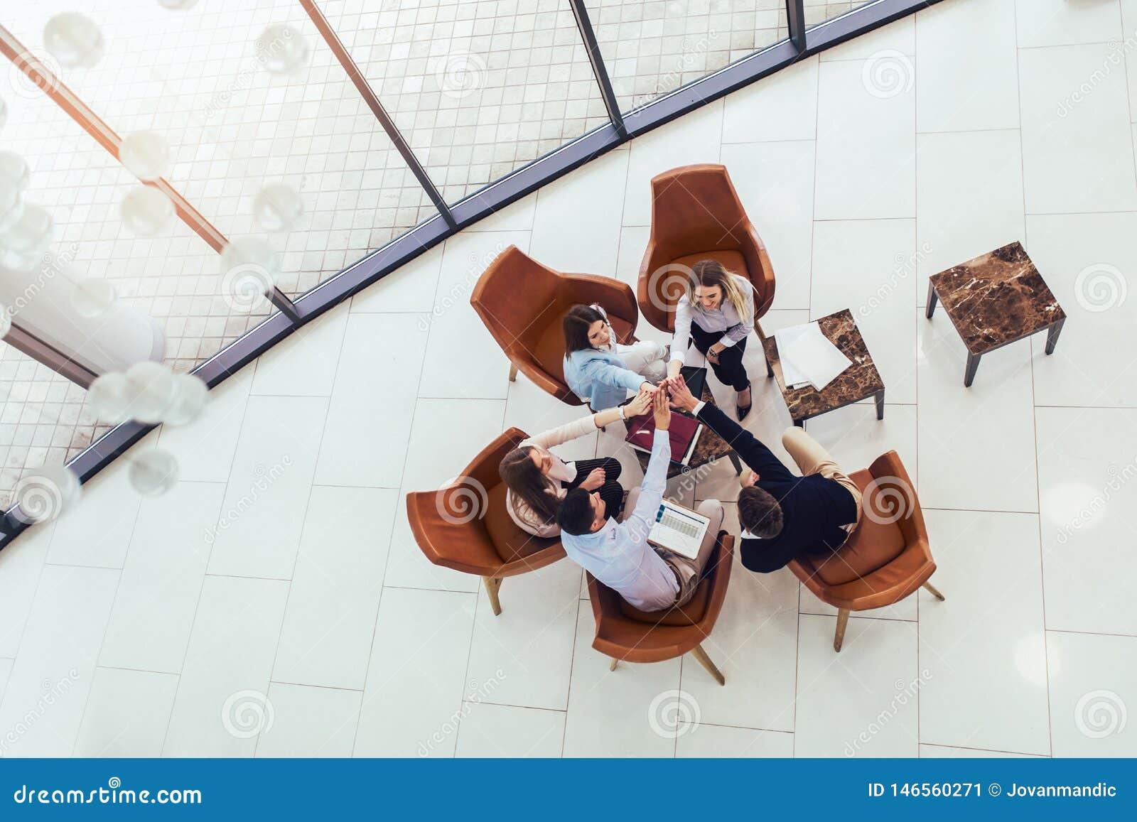 Grupa młodzi biznesowi profesjonaliści siedzi wpólnie i ma przypadkowy dyskutować w biurowym korytarzu Odg?rny widok