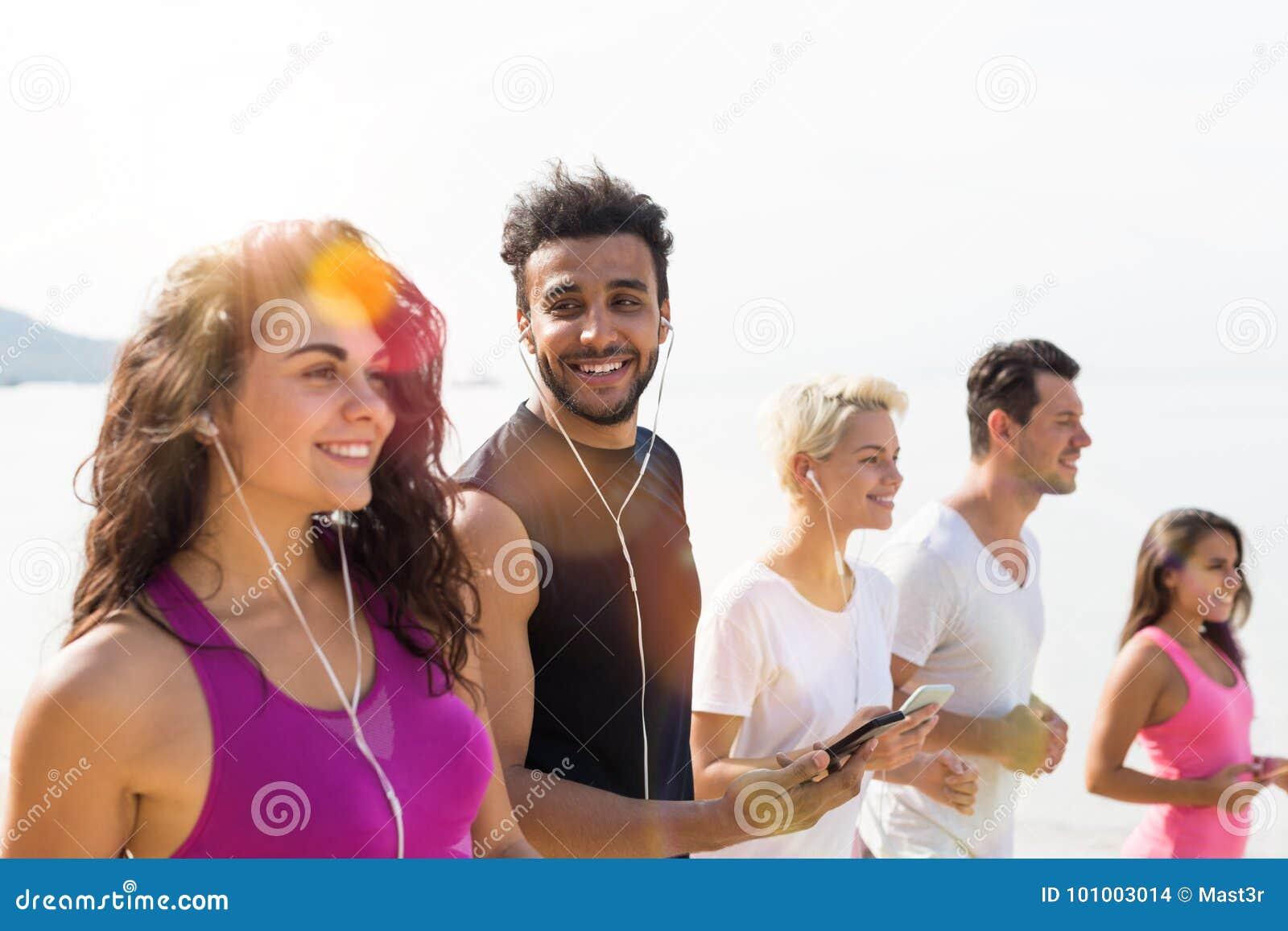 Grupa młodzi ludzie Biega Na Plażowy Szczęśliwy ono Uśmiecha się, mieszanki rasy sporta biegacze Jogging Pracującą sprawność fizy