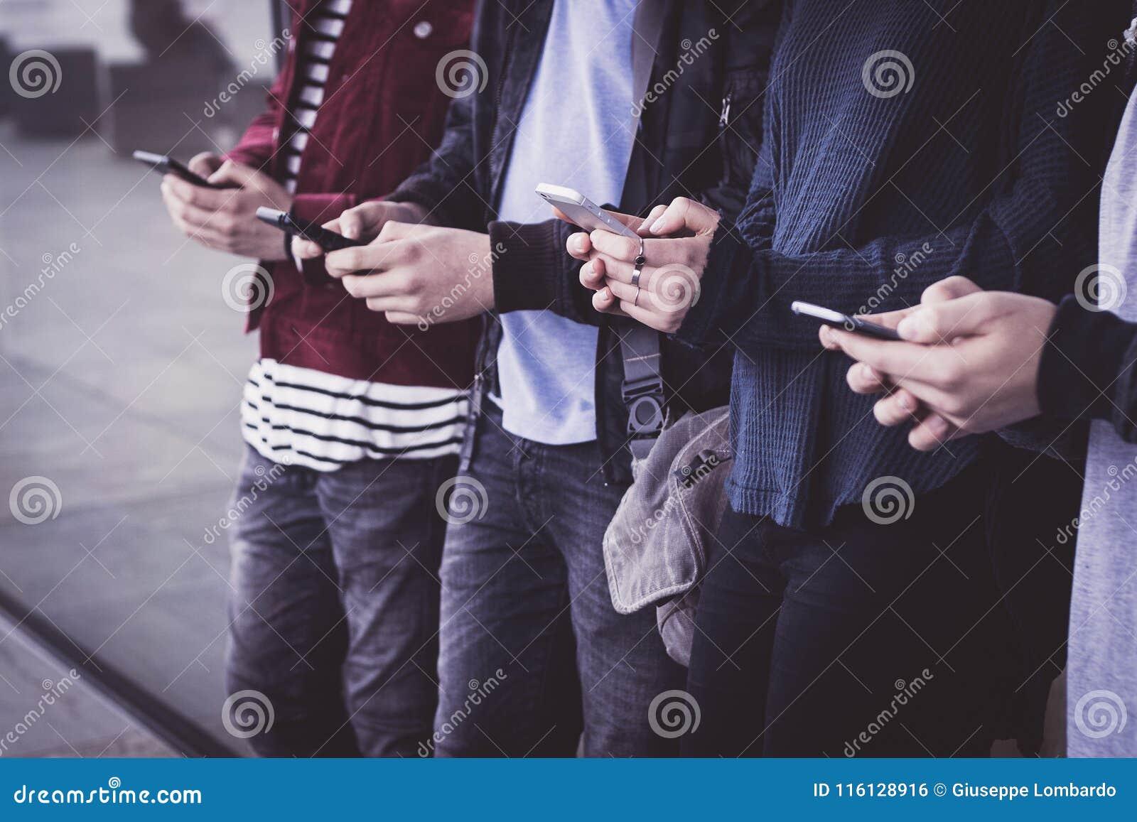Grupa młodzi ludzie ogląda mądrze telefony komórkowych przy underg