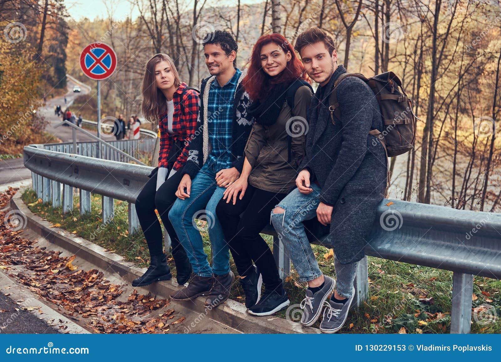 Grupa młodzi przyjaciele siedzi na poręczówce blisko drogi z piękną rzeką w tle i lasem z plecakami