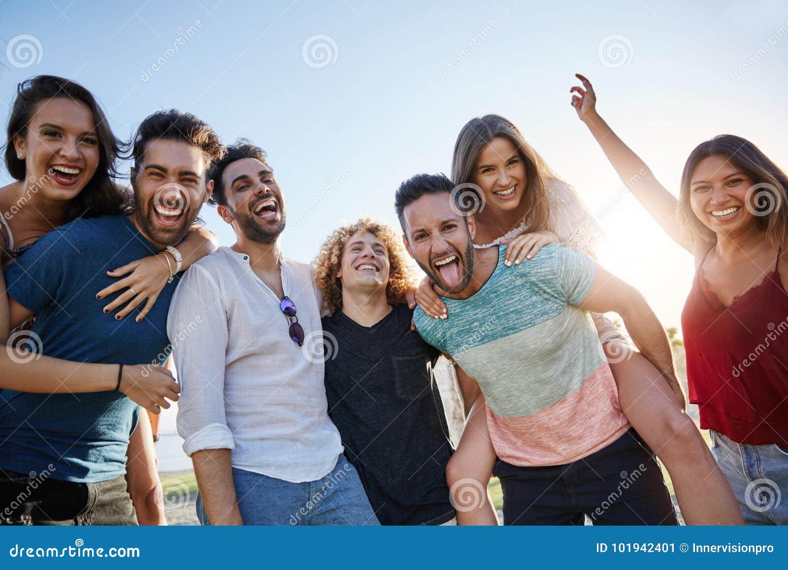 Grupa młodzi szczęśliwi ludzie stoi wpólnie outside