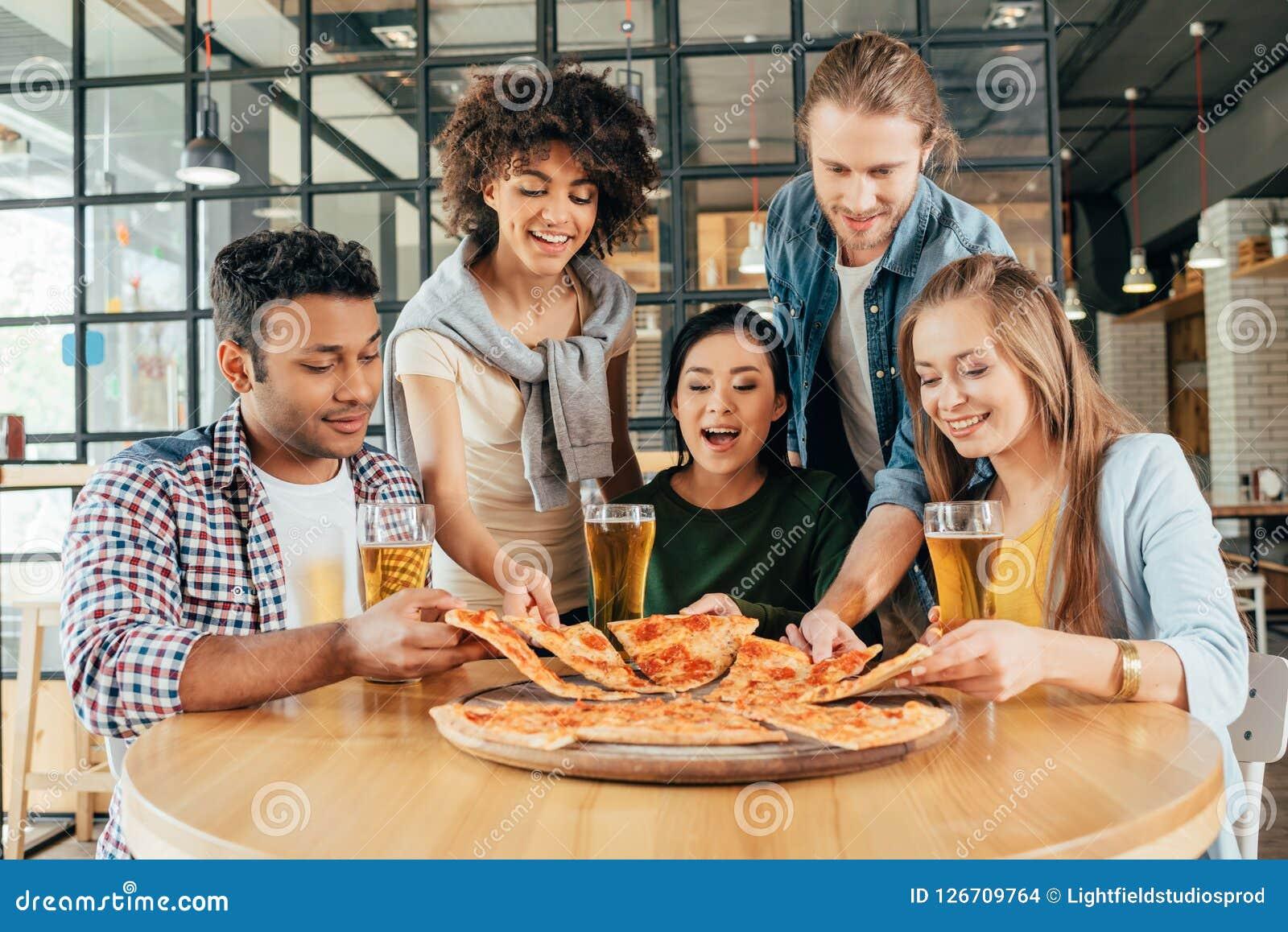 Grupa młodzi wieloetniczni przyjaciele ma pizzę