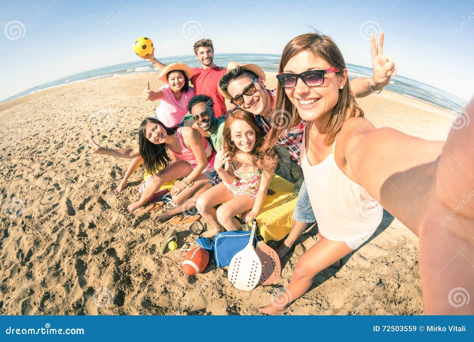 Grupa multiracial szczęśliwi przyjaciele bierze zabawy selfie przy plażą