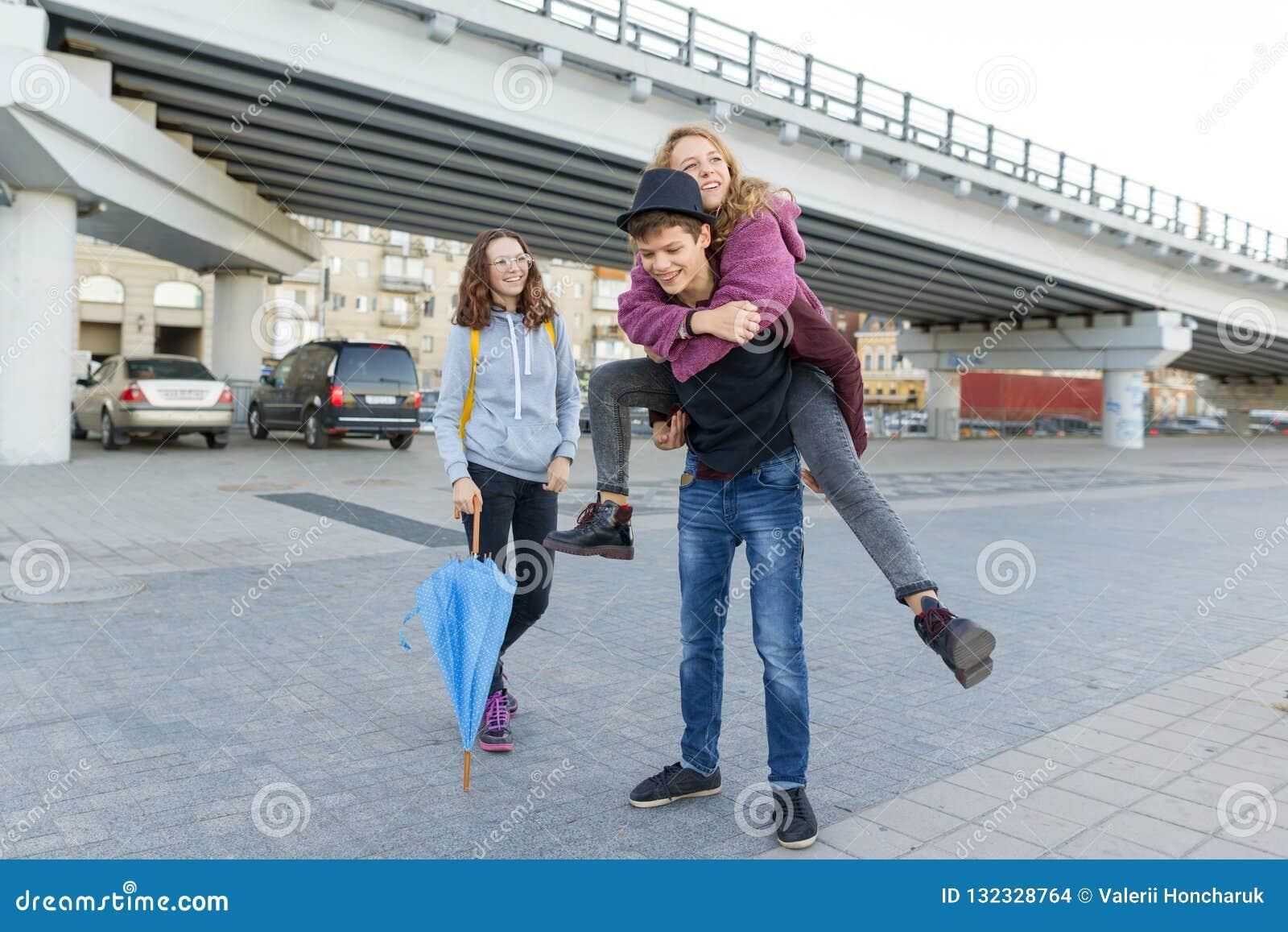 Grupa nastolatków przyjaciele ma zabawę w mieście, śmia się dzieciaków z parasolem Miastowy nastoletni styl życia