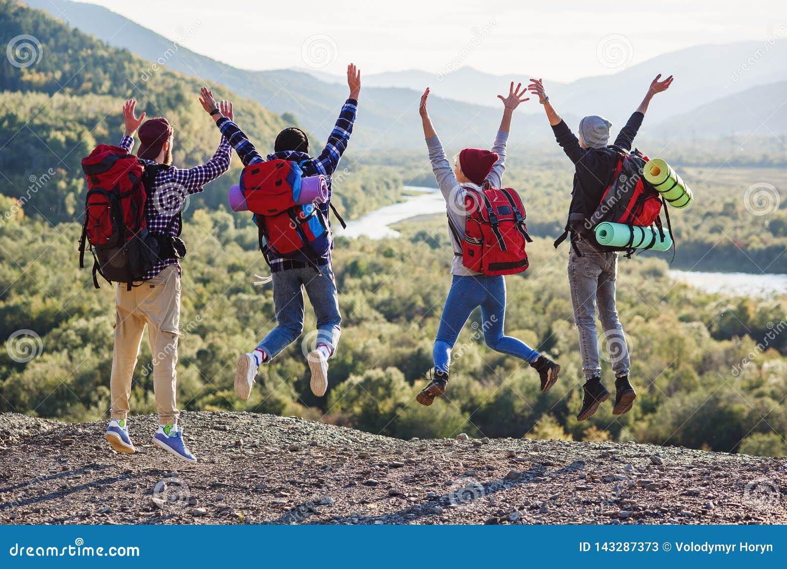 Grupa pięć szczęśliwych przyjaciół skacze przy zmierzchu czasem na tło górach