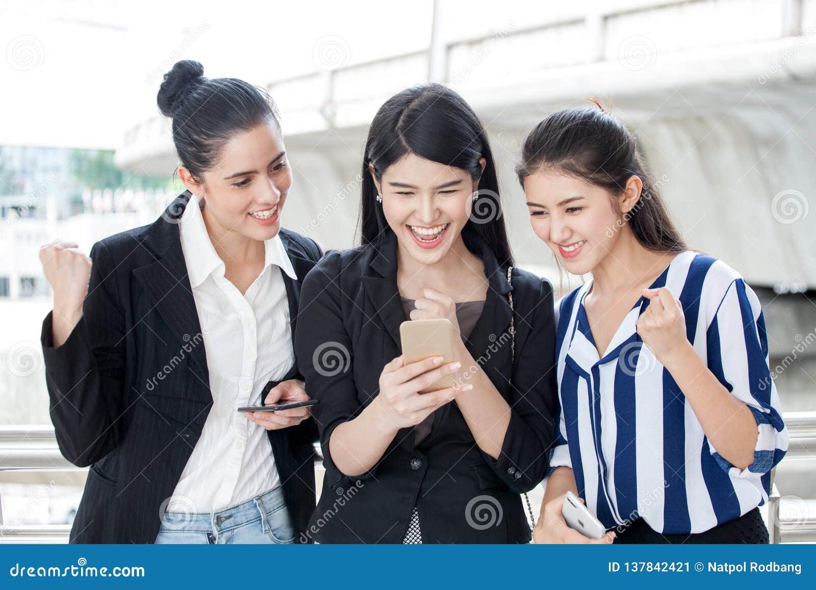 Grupa piękni młoda kobieta przyjaciele używa mądrze telefon i śmiający się outdoors trzy dziewczyny podniecającego biznesowego on