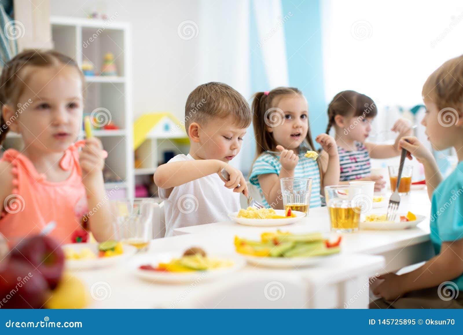 Grupa preschool dzieciaki lunch w daycare Dzieci je zdrowego jedzenie w dziecinu