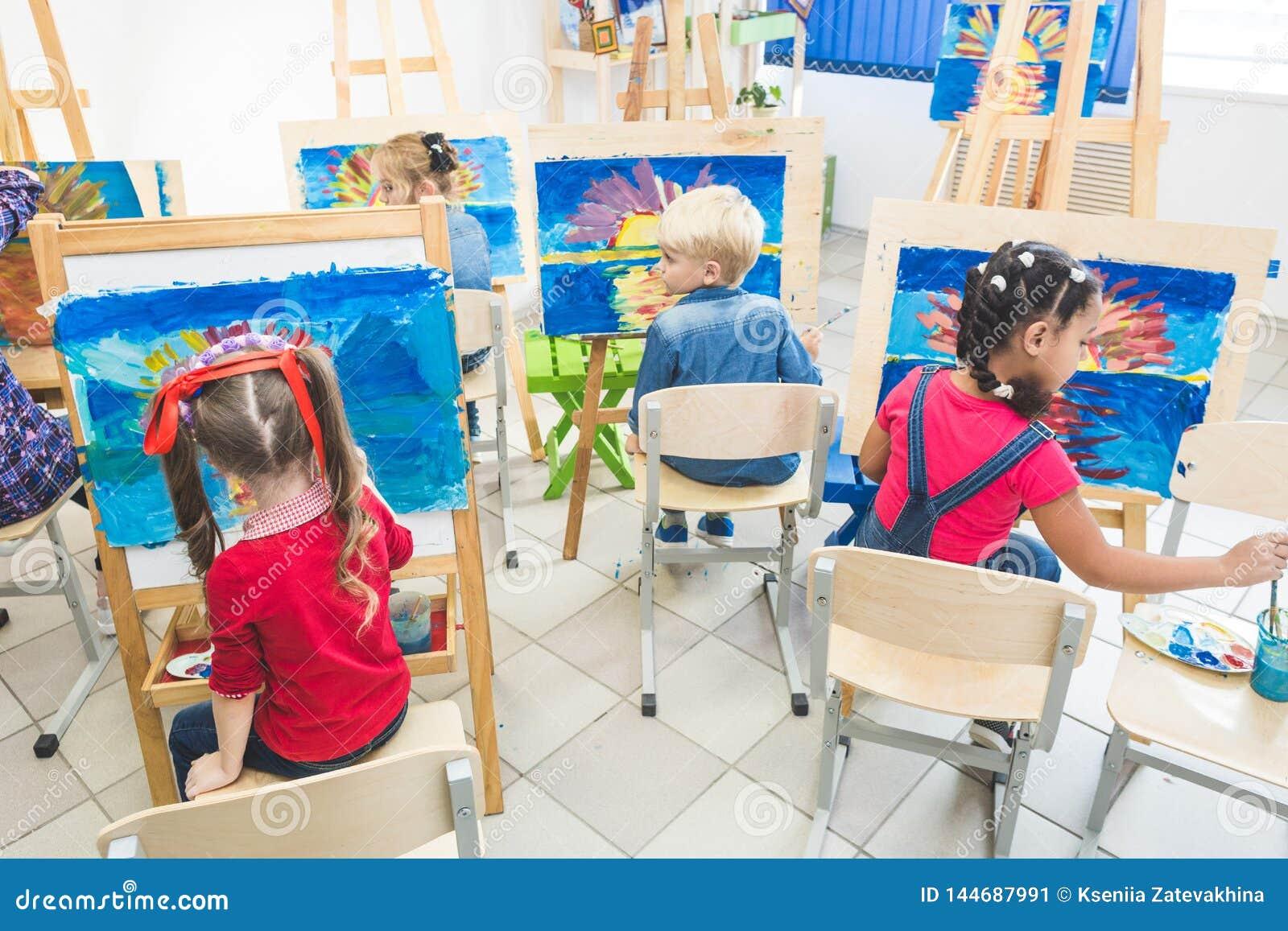 Grupa preschool ucznie i m?ody nauczyciel w rysunkowej klasie malujemy w guaszie mieszany biegowy uczennicy afroamerican