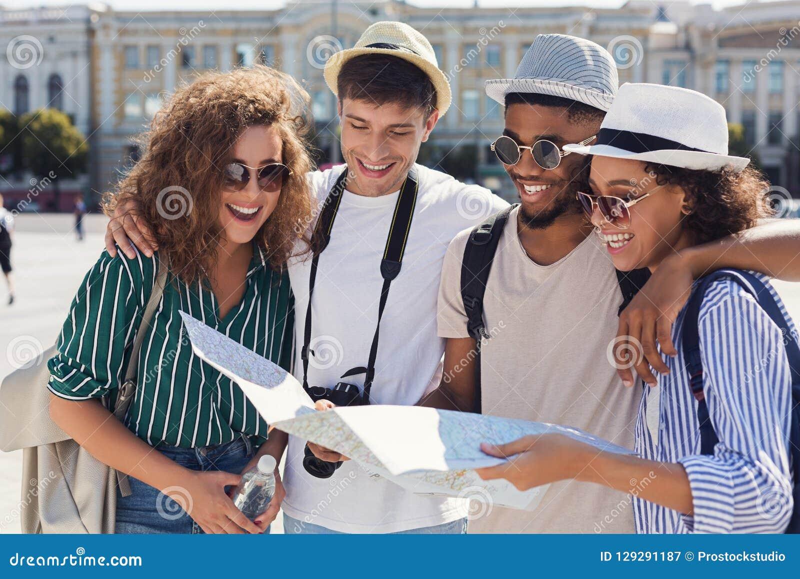 Grupa przyjaciele chodzi przez miasta z mapą