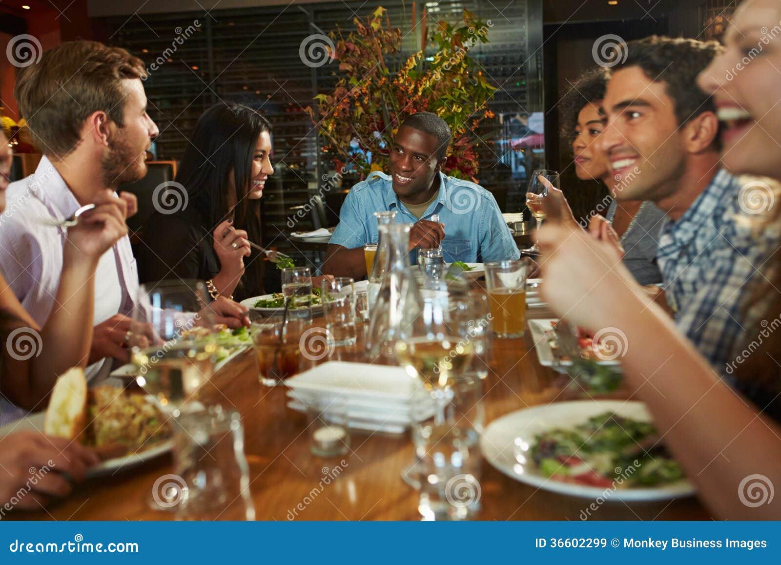 Grupa przyjaciele Cieszy się posiłek W restauraci