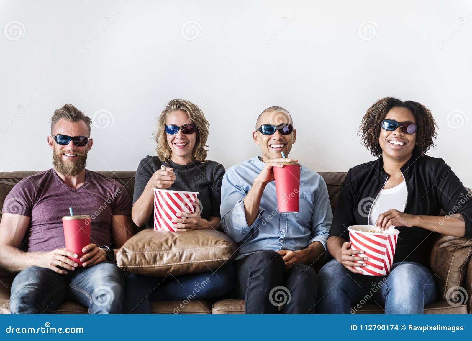Grupa przyjaciele ma zabawy dopatrywania film wpólnie