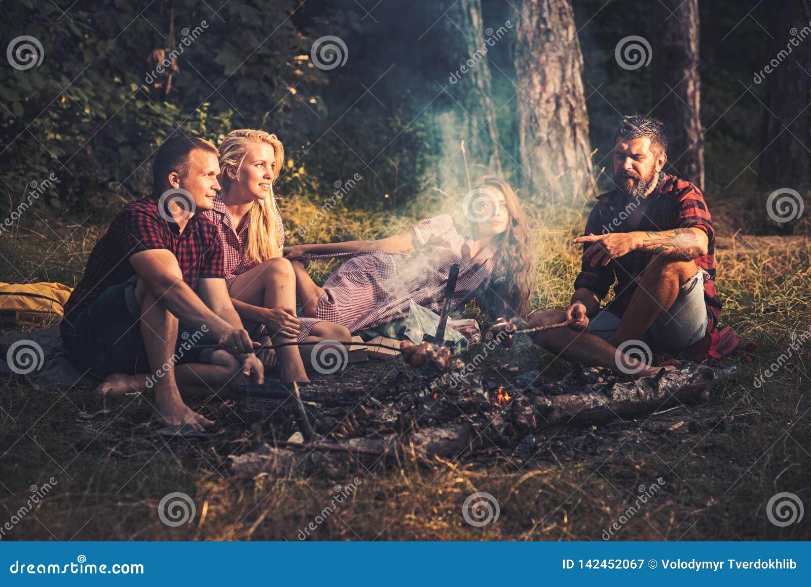 Grupa przyjaciele obozuje w lasu Dwa parach smaży kiełbasy na kijach Młodzienowie opowiada wokoło ogniska