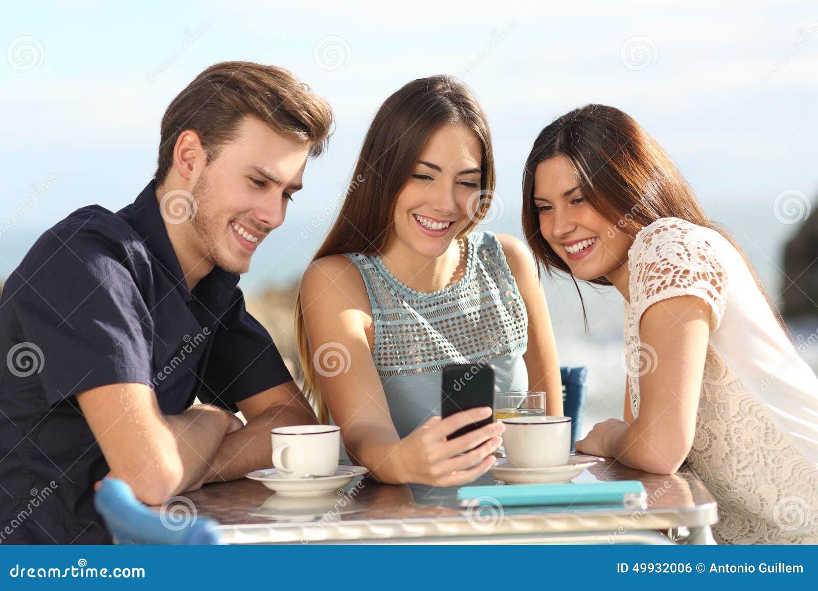 Grupa przyjaciele ogląda ogólnospołecznych środki w mądrze telefonie