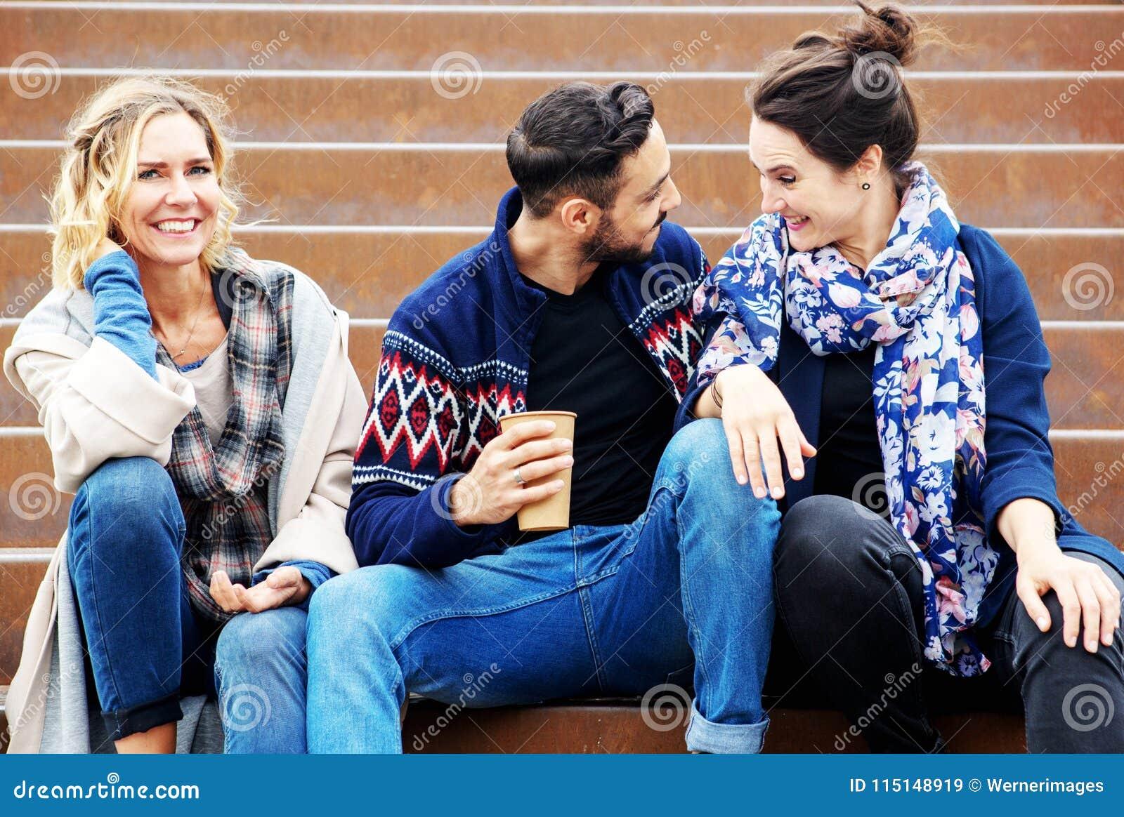 Grupa przyjaciele siedzi outside na schodkach