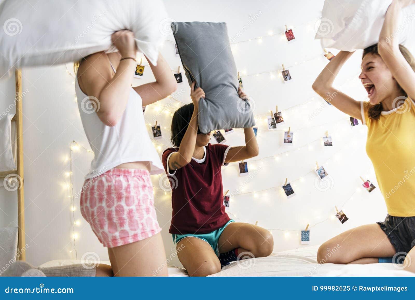 Grupa różnorodne kobiety bawić się poduszki walkę na łóżku wpólnie