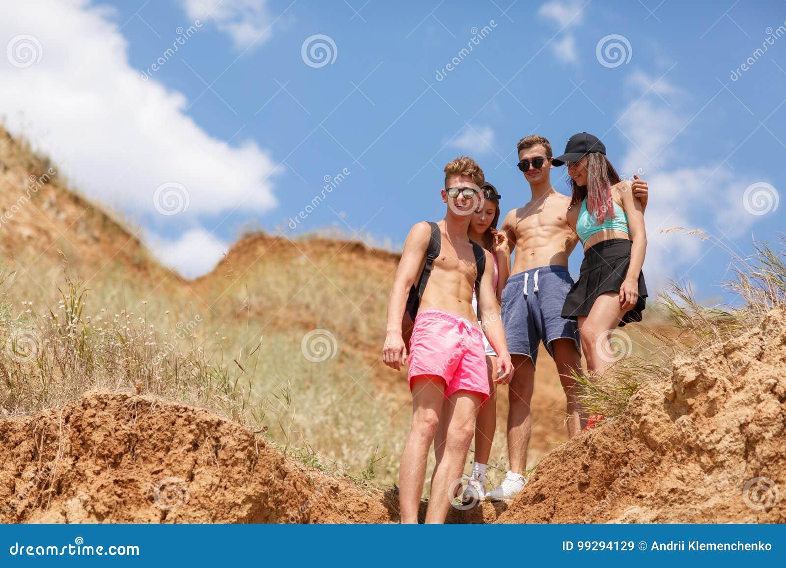 Grupa roześmiani przyjaciół stojaki na polu, pięknych dziewczynach i chłopiec na wakacje na naturalnym zamazanym tle,