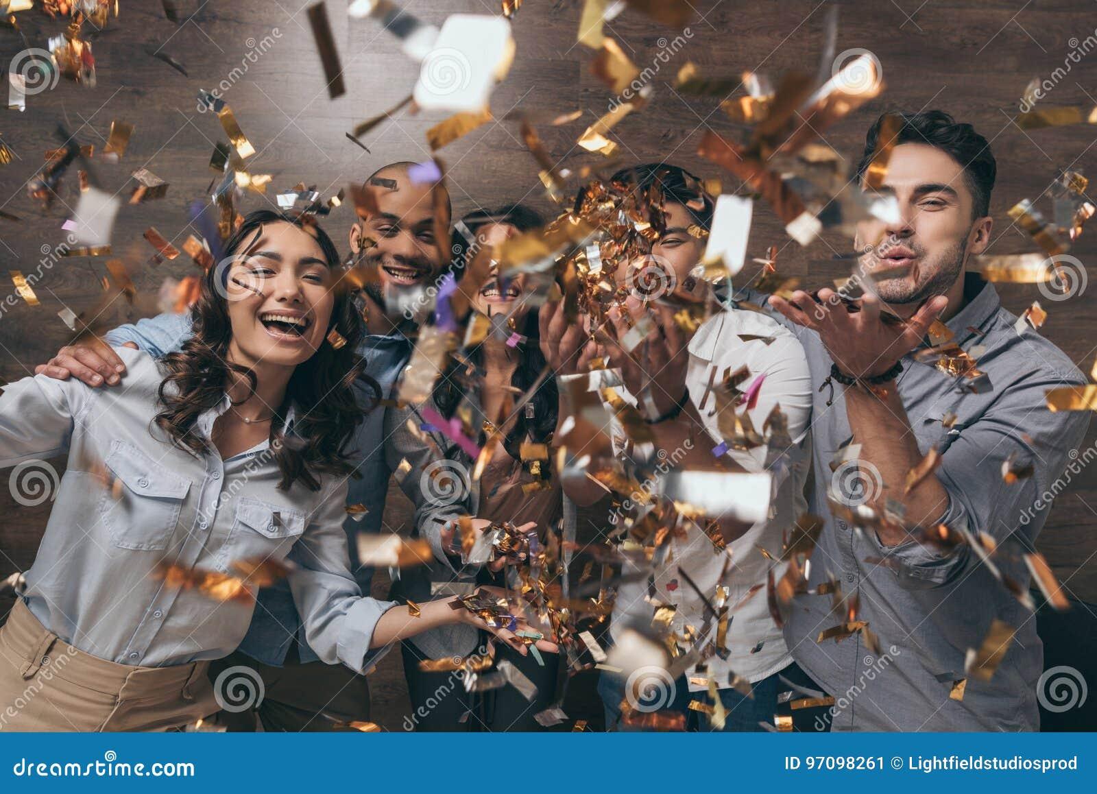 Grupa rozochoceni młodzi ludzie stoi wpólnie i świętuje z confetti