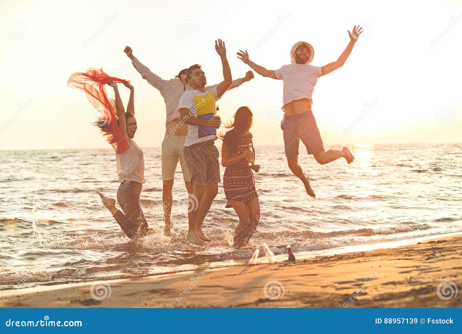 Grupa szczęśliwi młodzi ludzie tanczy przy plażą na pięknym lato zmierzchu