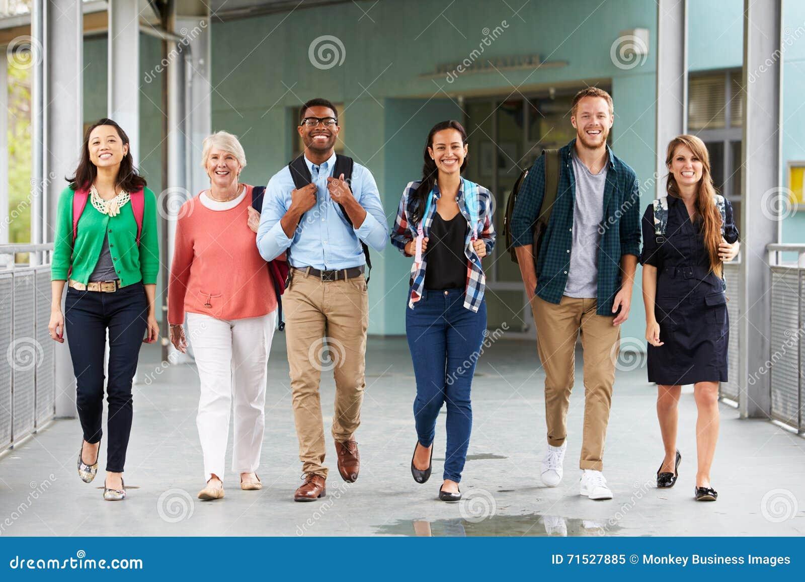 Grupa szczęśliwi nauczyciele chodzi w szkolnym korytarzu