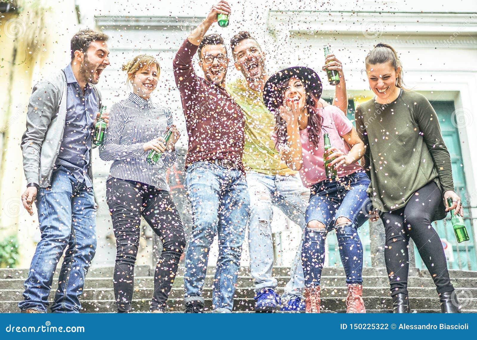 Grupa szczęśliwi przyjaciele robi przyjęcia śmia się wpólnie i pije piwa plenerowych na obszarze miejskim - młodzi ludzie ma zaba
