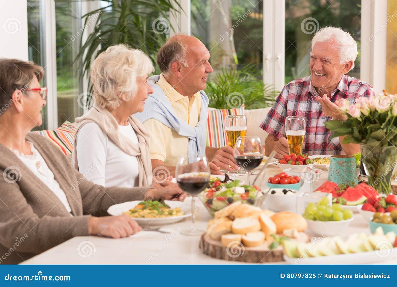 Grupa szczęśliwi seniory je gościa restauracji