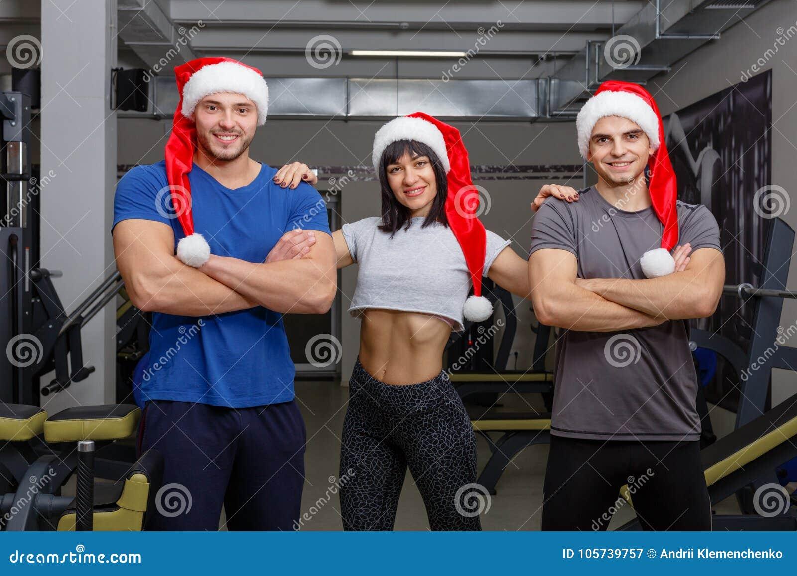 Grupa szczęśliwi sportowowie w Bożenarodzeniowych kapeluszach, pozować trwanie i uśmiechnięty Indoors w gym