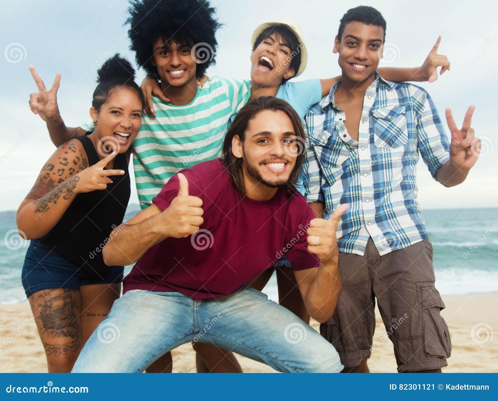 Grupa szczęśliwi wielo- etniczni młodzi dorosli ludzie przy plażą