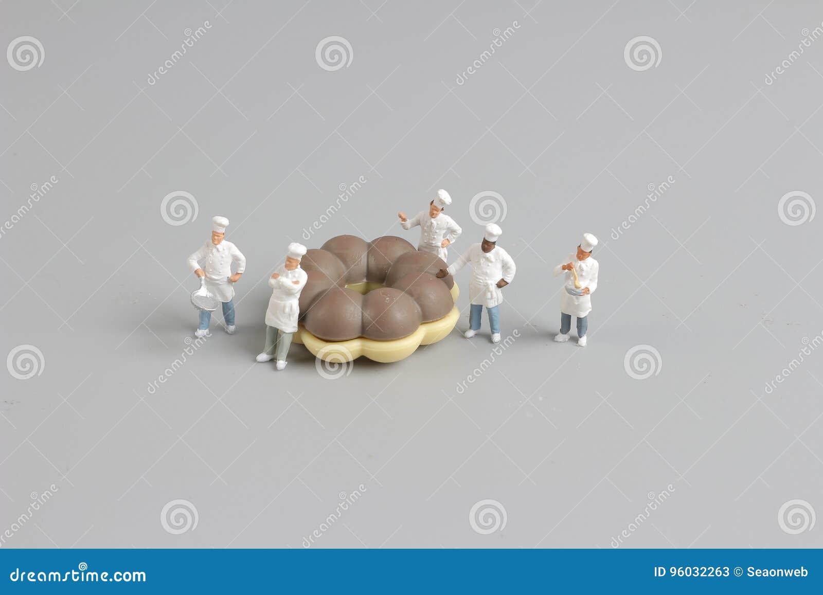 Grupa szefowie kuchni wokoło małych donuts