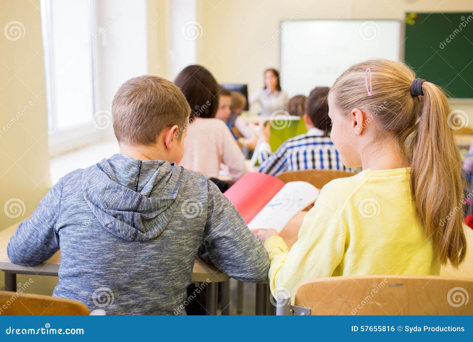 Grupa szkoła żartuje writing test w sala lekcyjnej