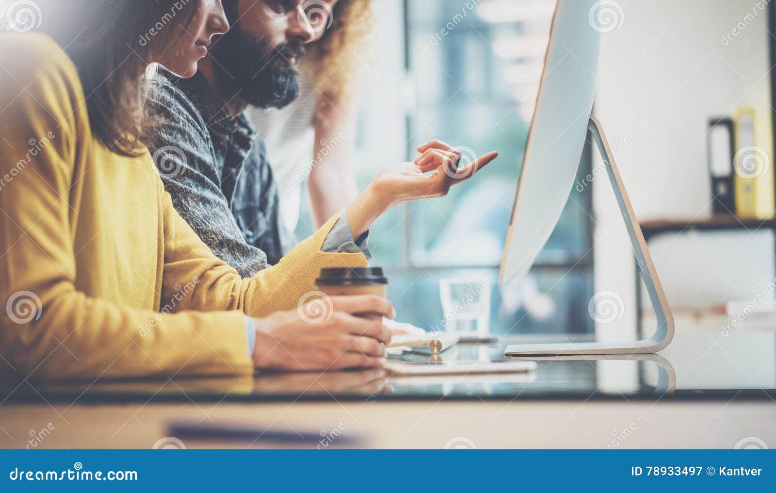 Grupa trzy młodego coworkers pracuje wpólnie w pogodnym biurze Mężczyzna pisać na maszynie na komputerowej klawiaturze Kobieta ws