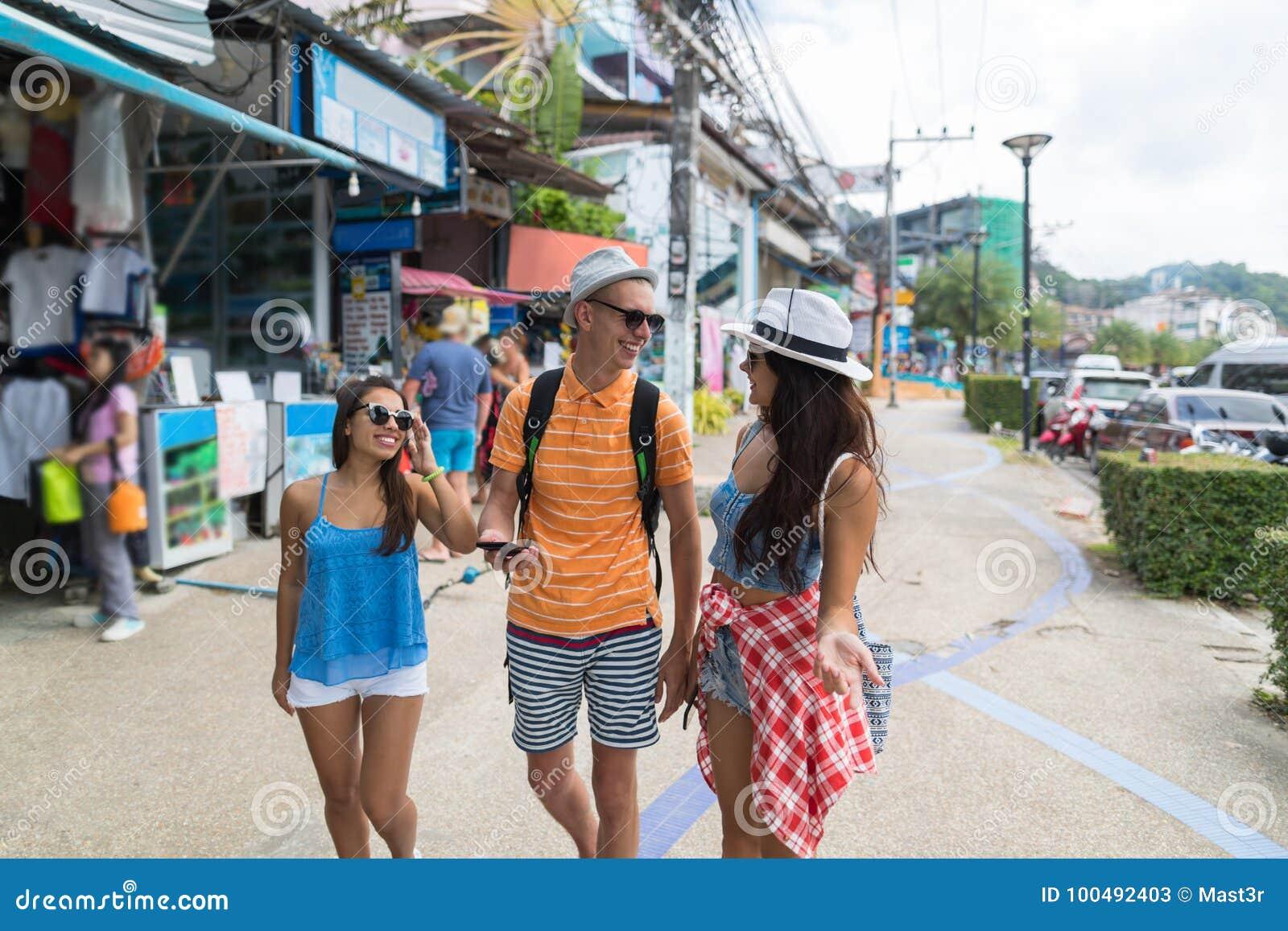 Grupa turyści Chodzi ulicę Wpólnie Patrzeje Dla właściwej wskazówki W telefonie komórkowym Azjatycki miasto
