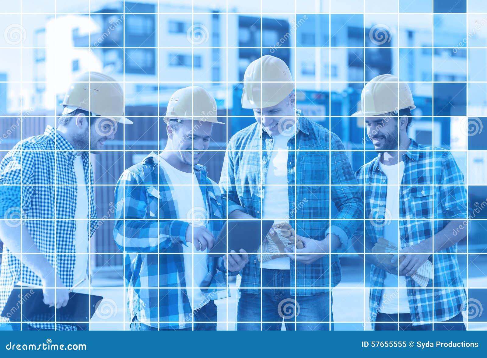 Grupa uśmiechnięci budowniczowie z pastylka komputerem osobistym outdoors