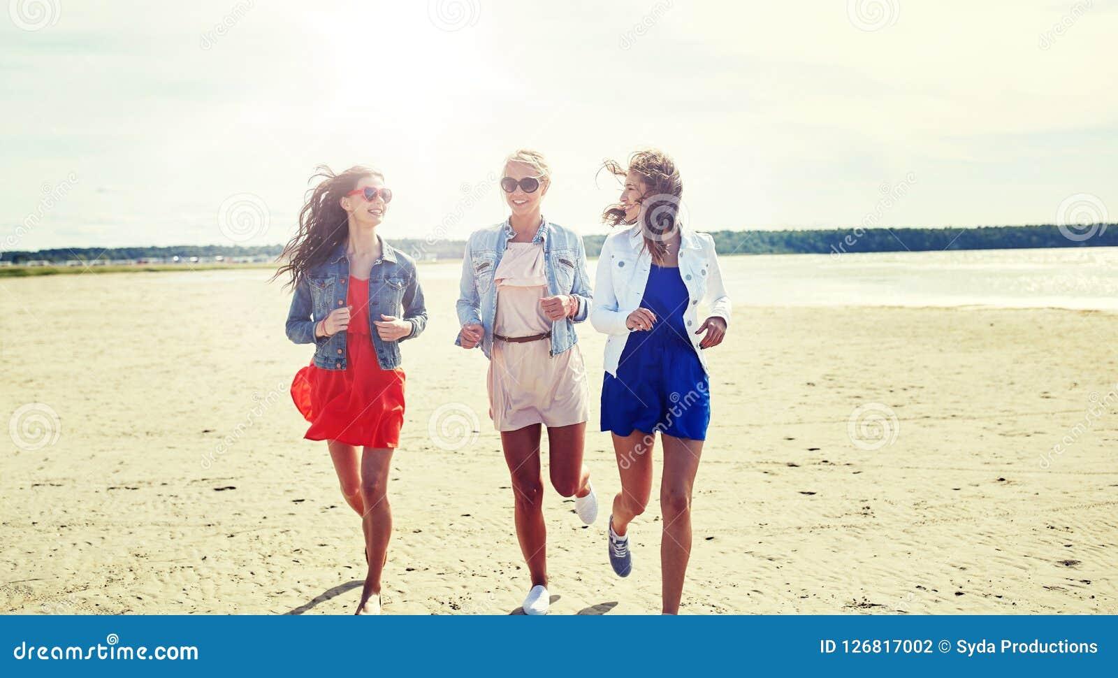 Grupa uśmiechnięte kobiety w okularach przeciwsłonecznych na plaży