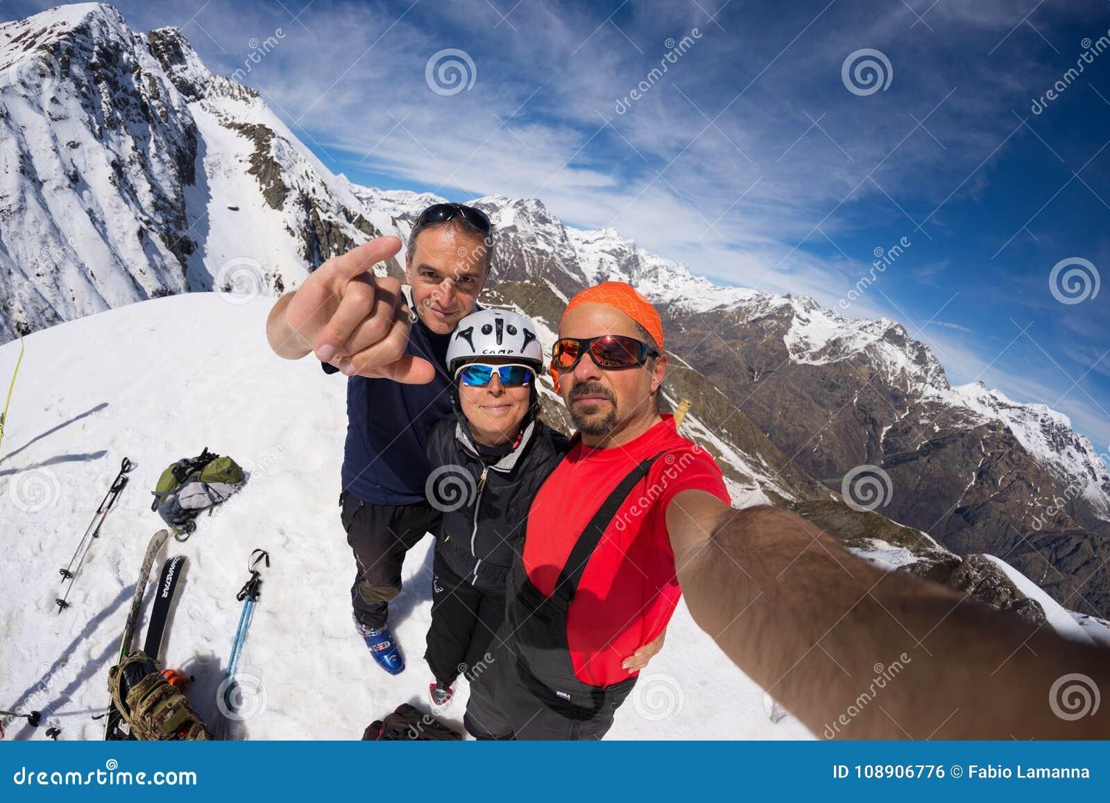 Grupa wysokogórzec selfie na góra wierzchołku Sceniczny dużej wysokości tło na śniegu nakrywał Alps, słoneczny dzień