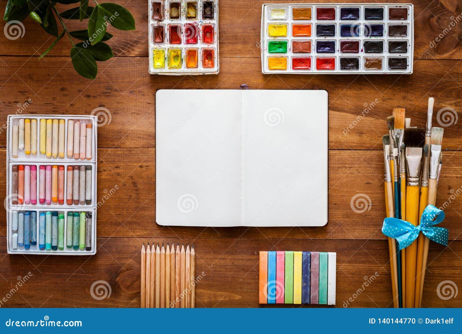 Grupo acessório criativo das fontes do trabalho de arte, caderno aberto para o esboço, escovas de pintura, paintbox com aquarelas