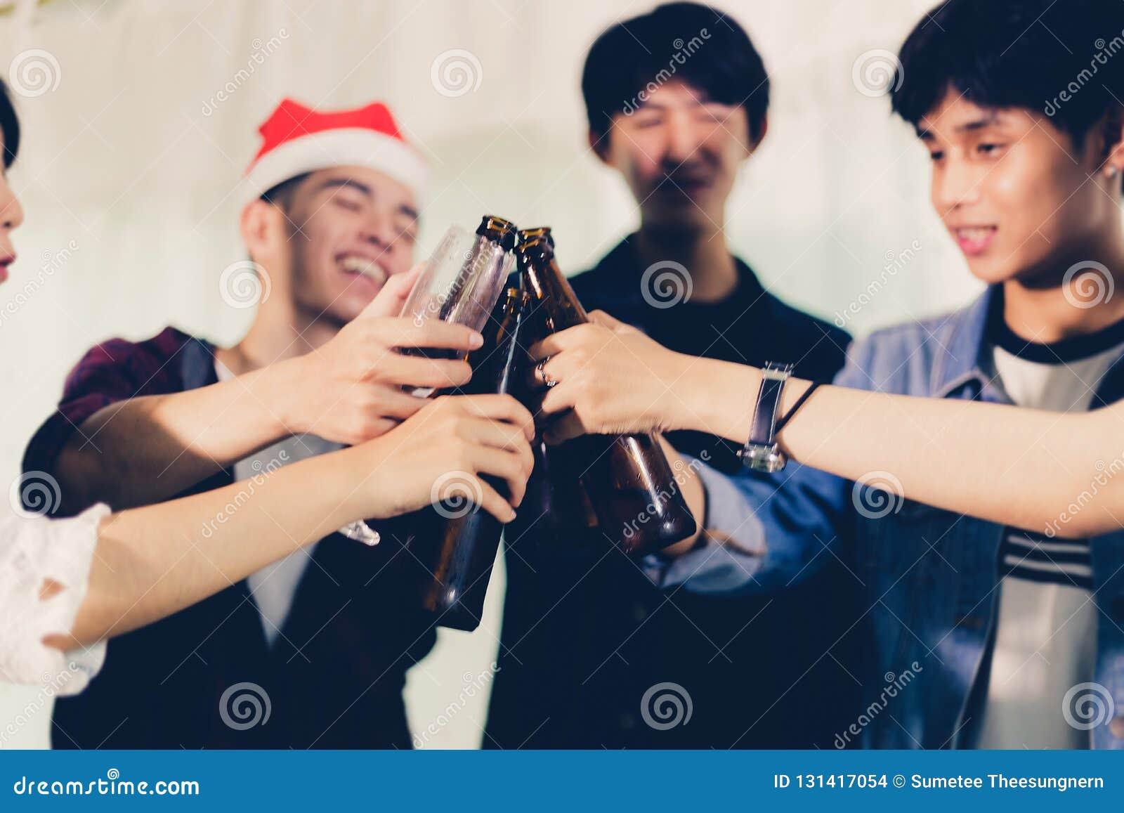 Grupo asiático de amigos que têm o partido com bebidas alcoólicas da cerveja e os jovens que apreciam em uma barra que brinda coc