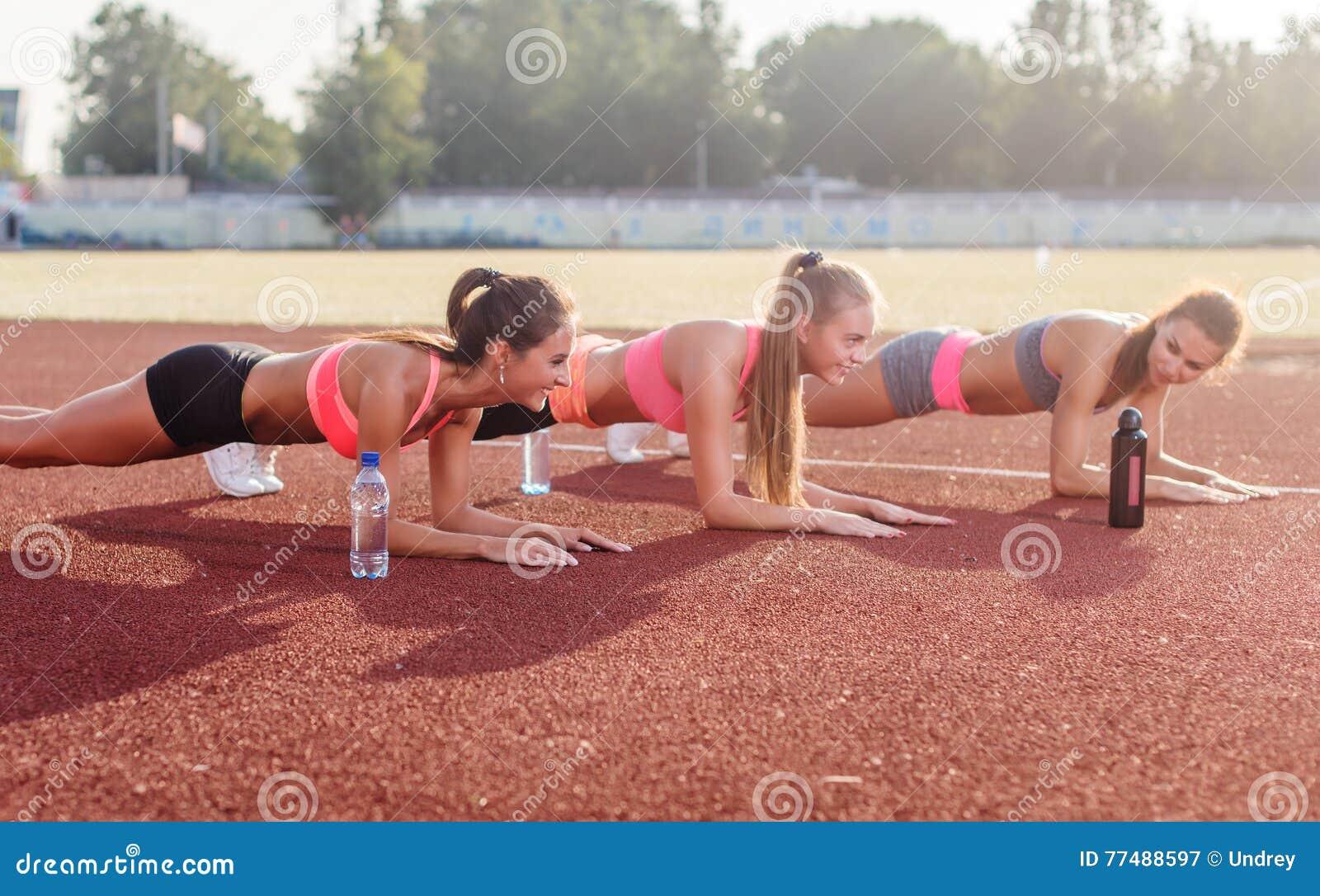 Grupo atlético de mujeres que entrenan en un día soleado que hace ejercicio del tablaje en el estadio