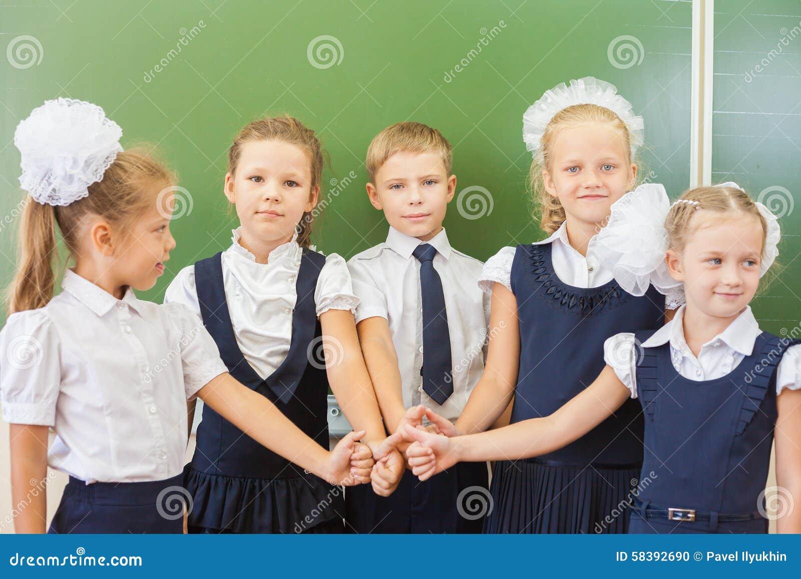 Grupo bem sucedido de crianças na escola com o polegar acima do gesto