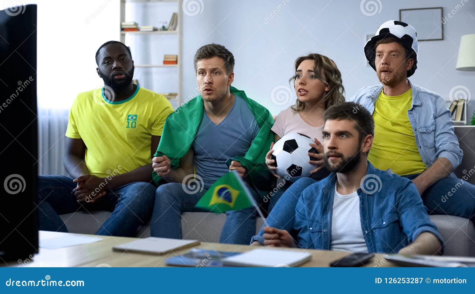 Grupo brasileño de amigos que miran el partido de fútbol en la TV en casa, unidad