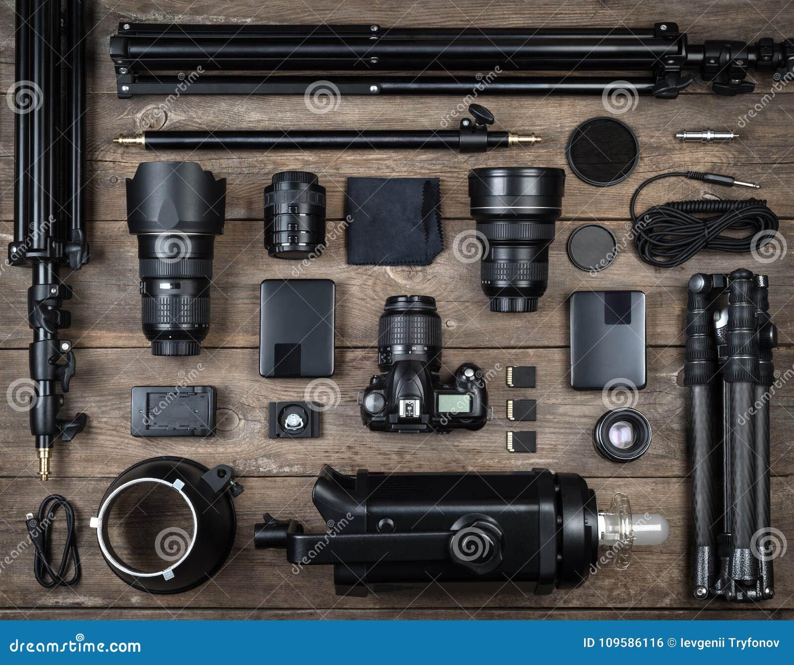 Grupo da câmera e da lente do equipamento da fotografia, tripé, filtro, flash, cartão de memória, mesa dura, refletor na mesa de