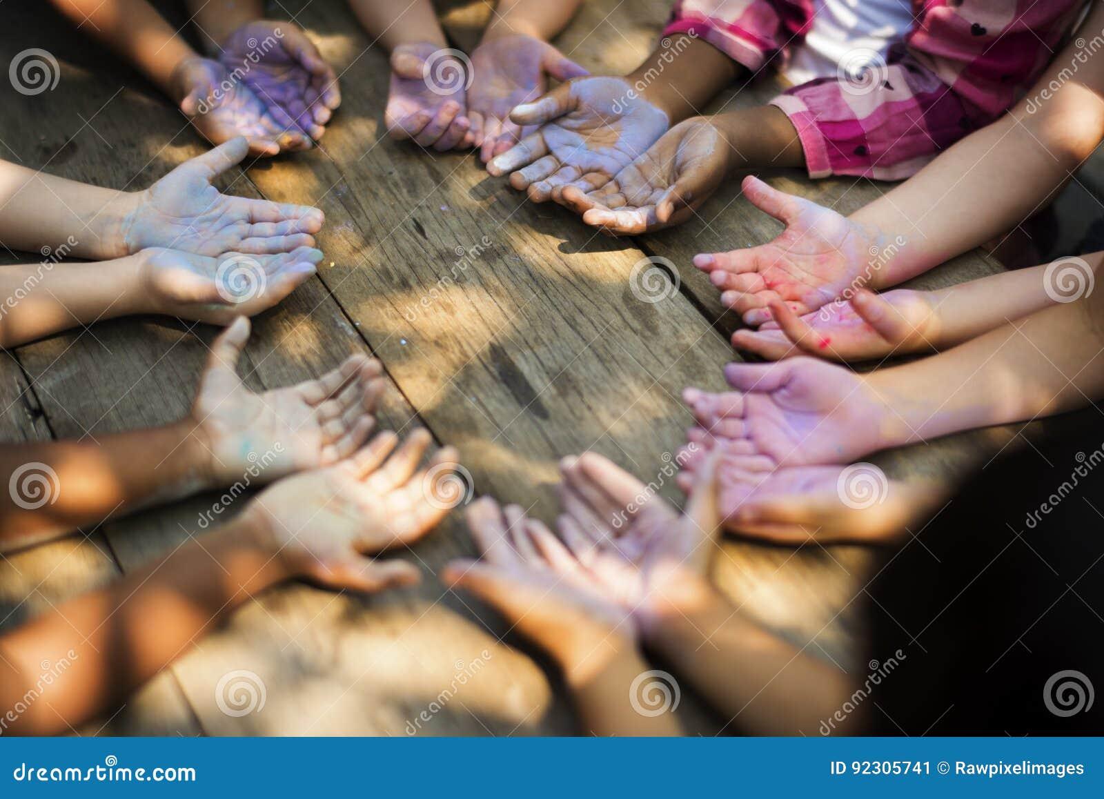 Grupo da diversidade de crianças que guardam as mãos no giz do círculo